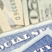 Clipped image of the edge of some social security cards on top of US currency.